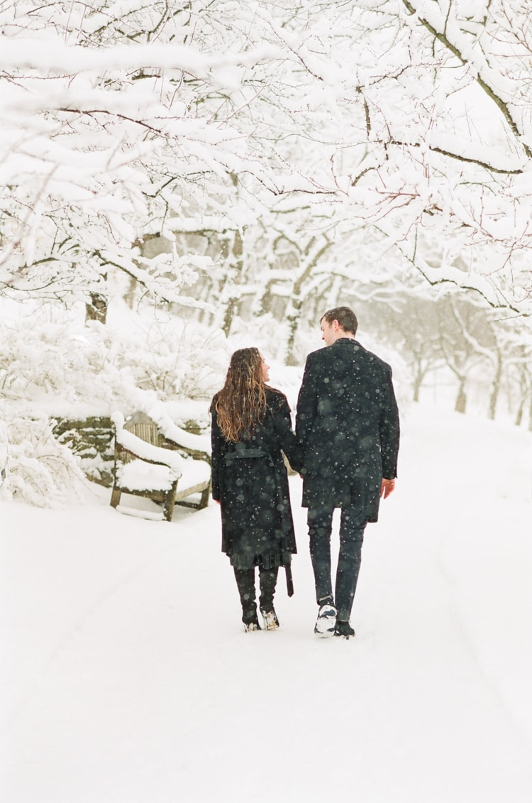 Engaged couple walking hand in hand at the Chicago Botanic Garden covered in snow