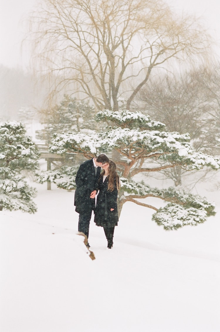 Engaged couple walking in snow at the Japanese Garden in Chicago