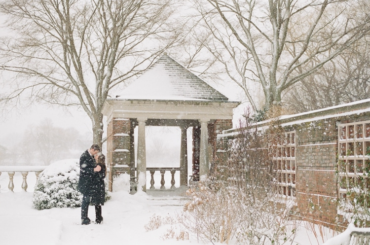 Engaged couple kissing at the English Walled Garden covered in snow