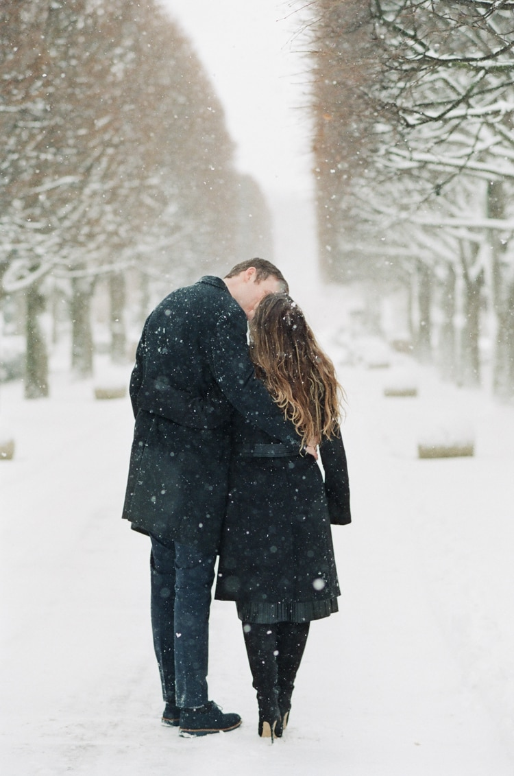 Engaged couple walking at the Rose Terrace at the Chicago Botanic Garden covered in snow