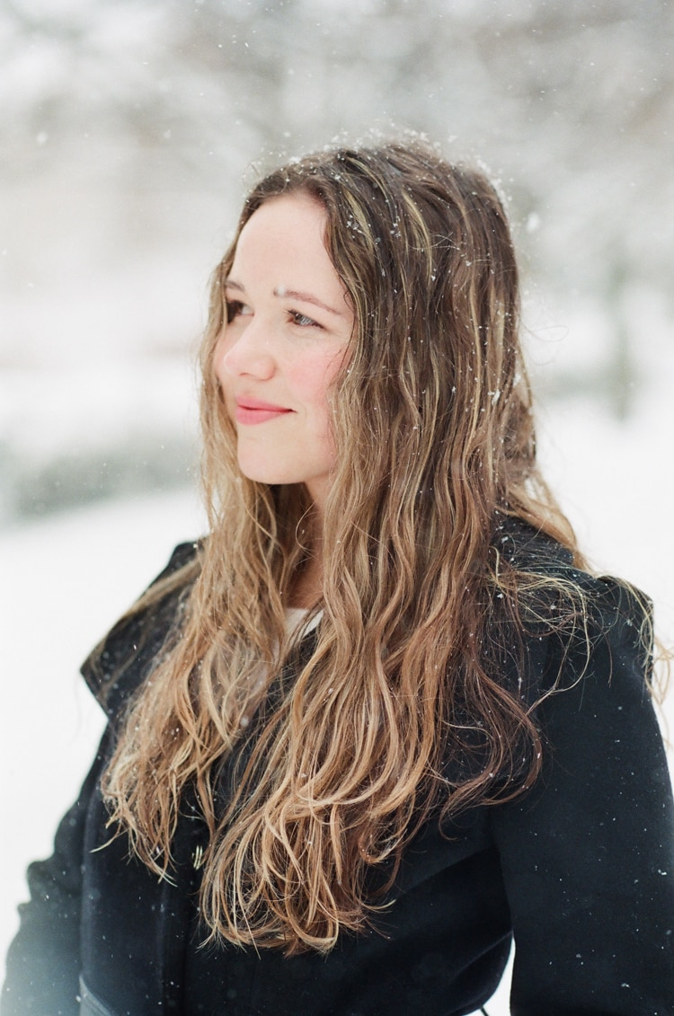 Bride to be wearing a black coat and standing in snow