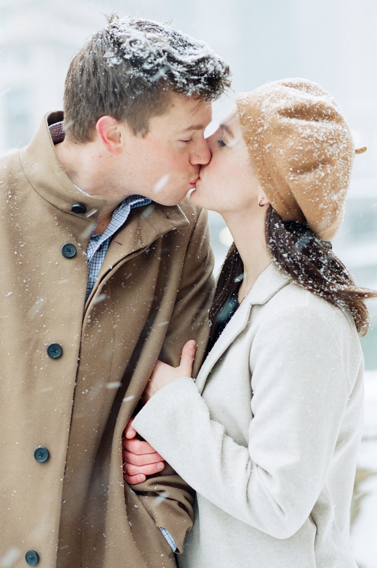 Engaged couple kissing each other at their Chicago downtown winter engagement