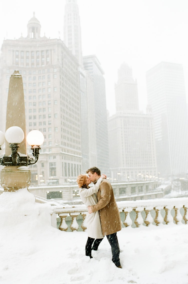Engaged couple kissing each other at Wrigley Building during snow