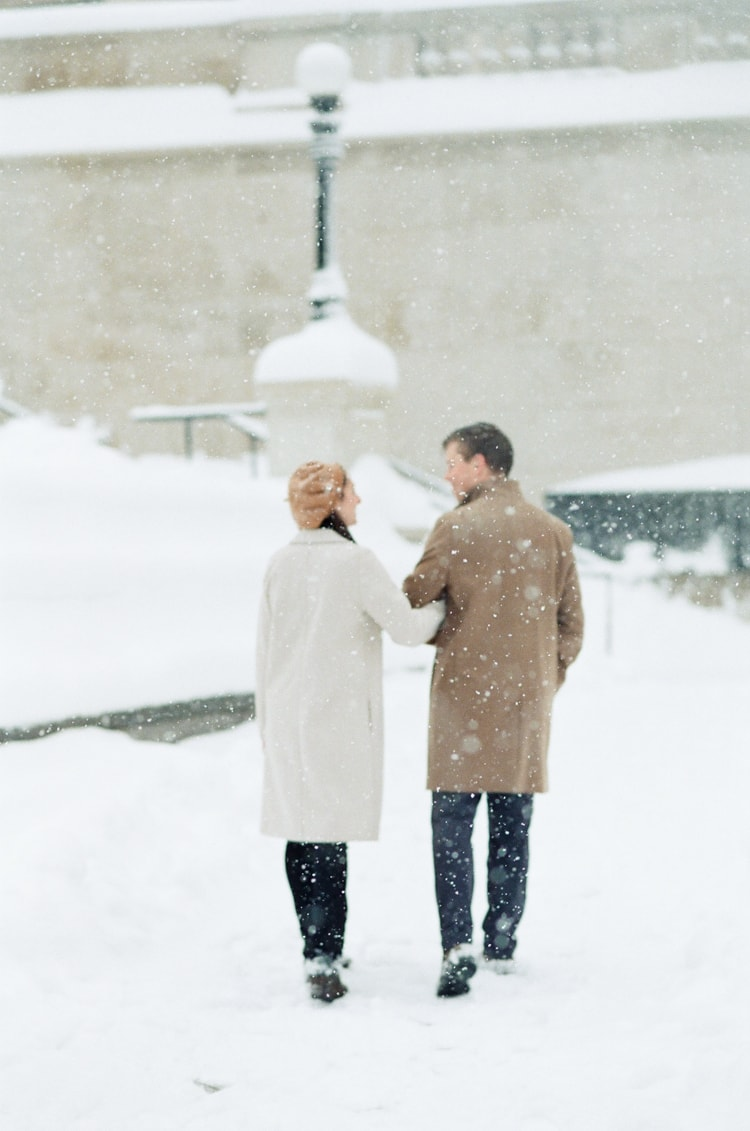 Bride and groom walking arm in arm during snowfall at Chicago Riverwalk