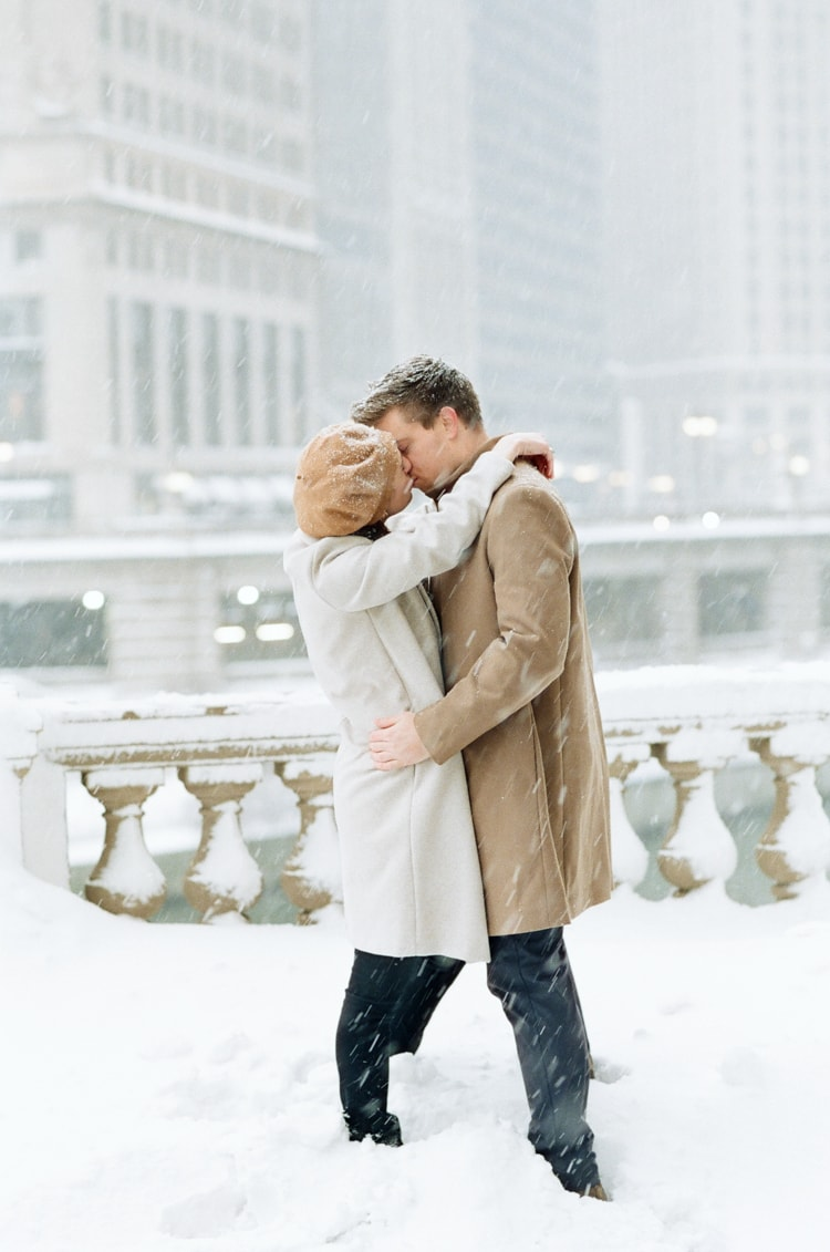 Engaged couple embracing each other while standing in snow