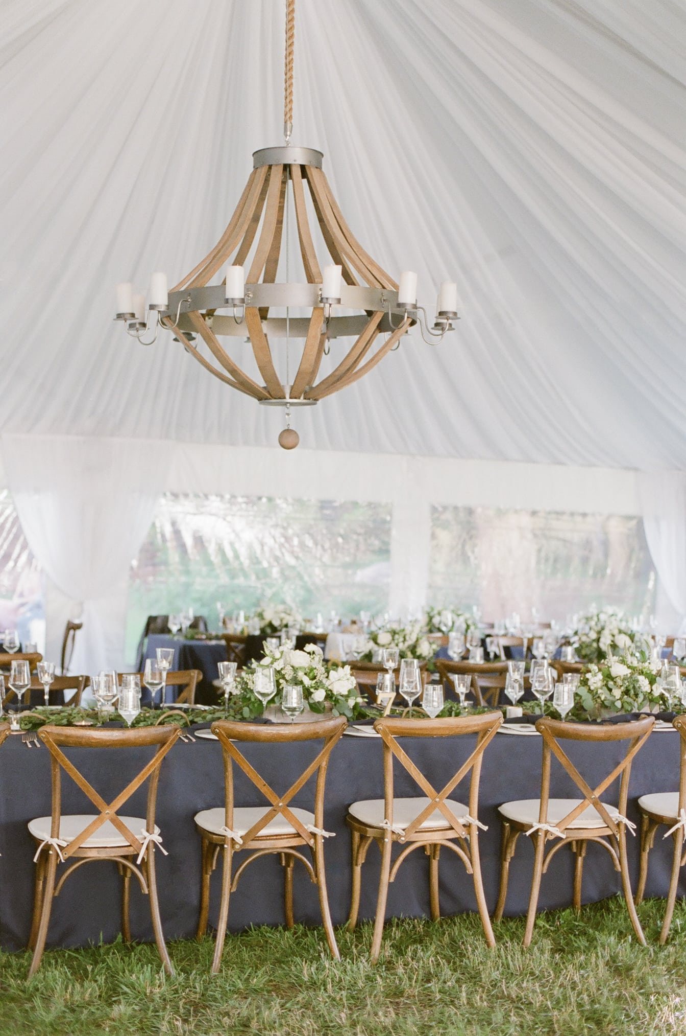 Tent wedding reception tablescape with blue table linen
