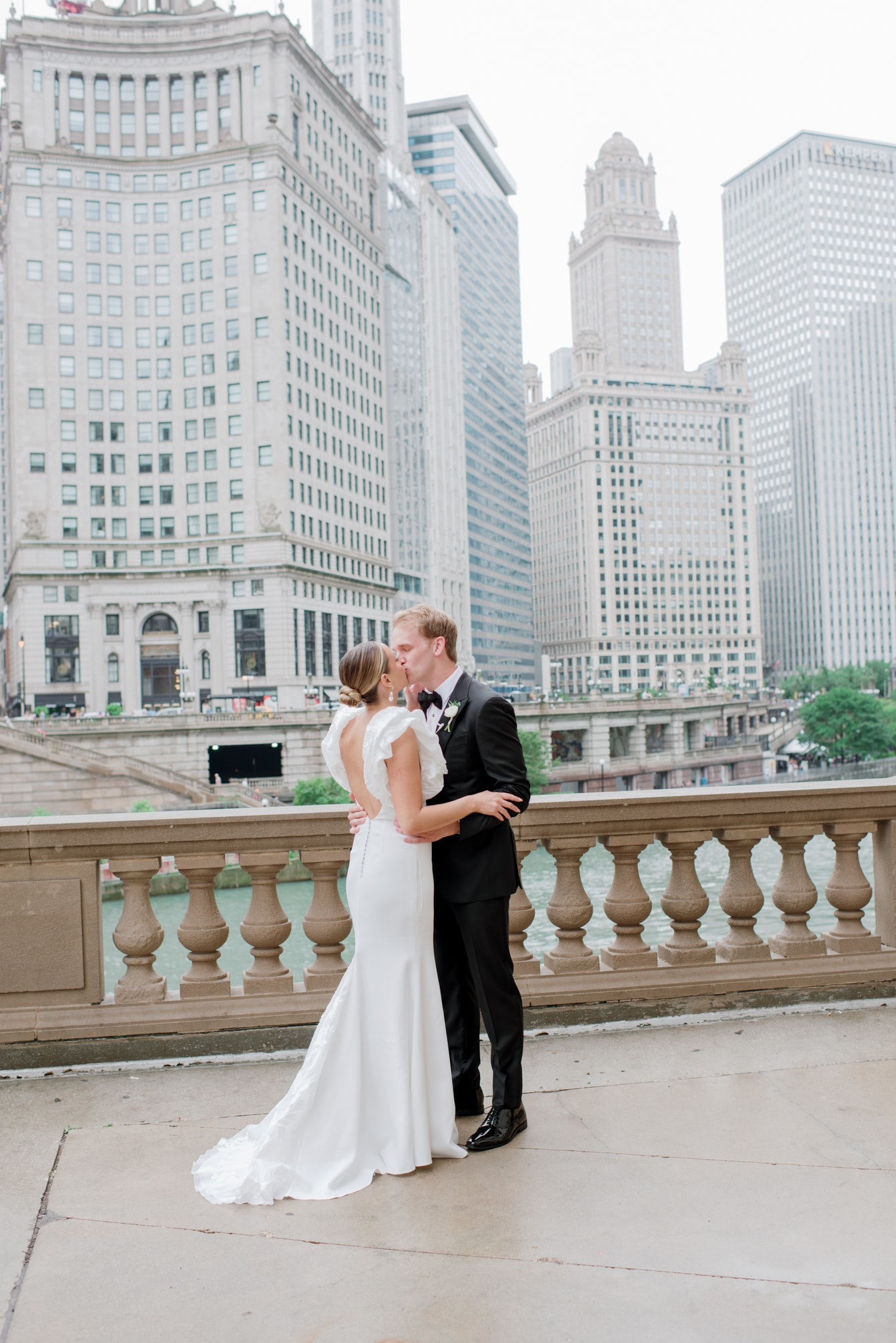 Bride and groom kissing in front of Chicago city view at Wrigley Building