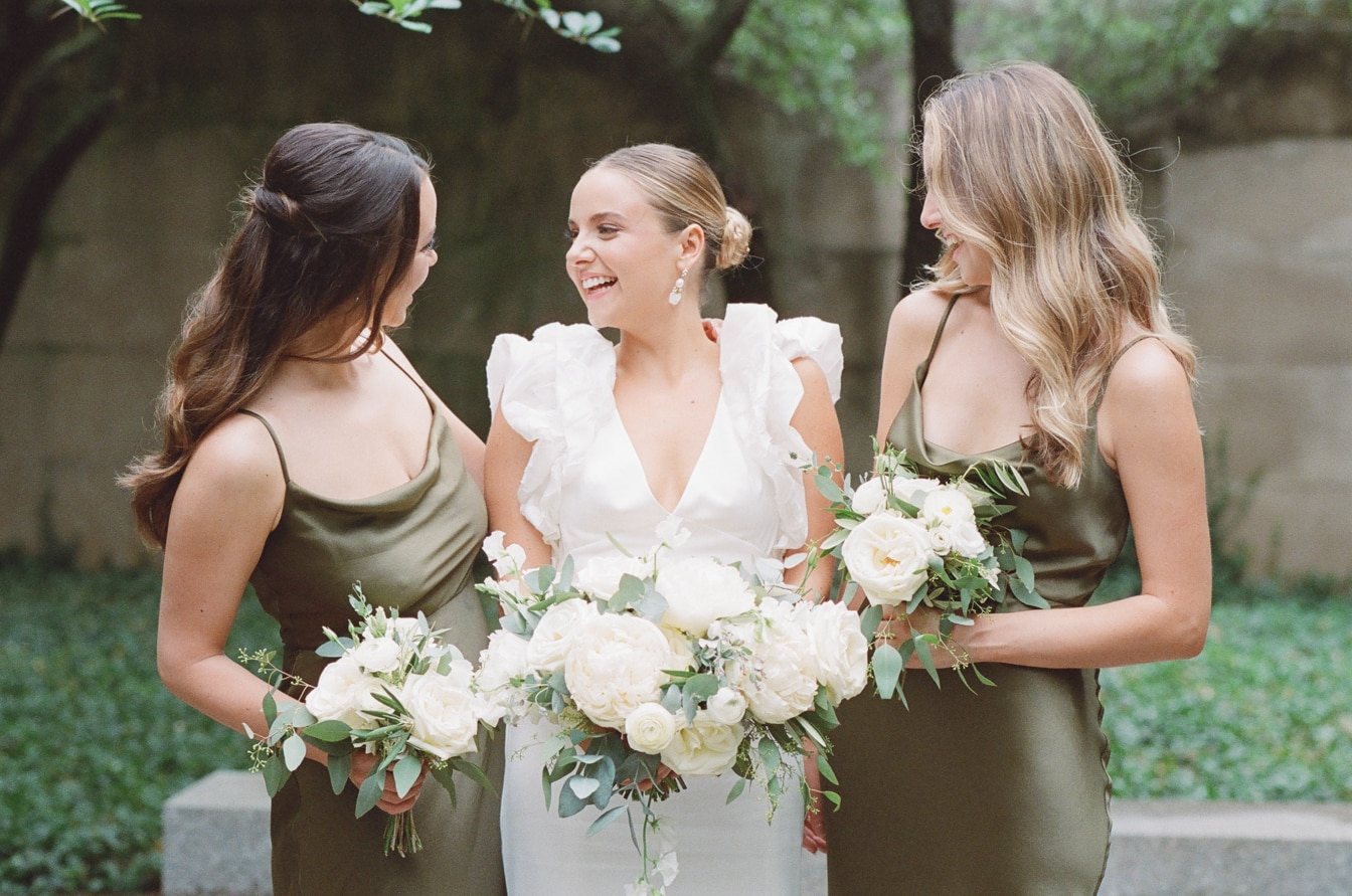 Bride smiling with her sisters while holding their bouquets