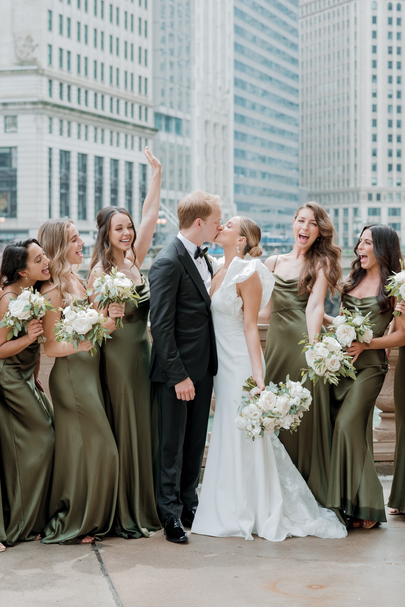 Bride and groom kissing amongst bridal party