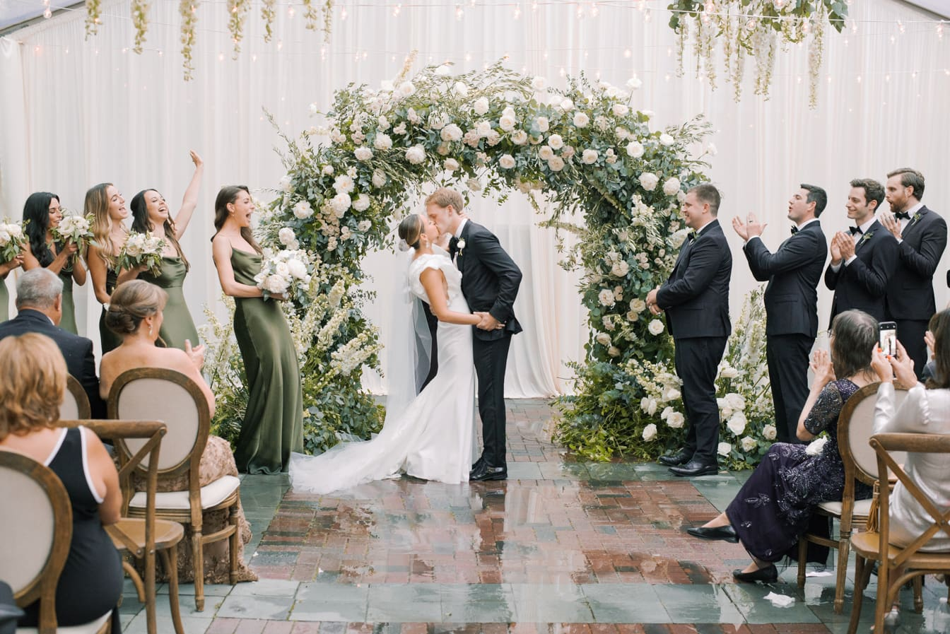 Bride and groom kissing each other under floral wedding arch after saying 'yes'