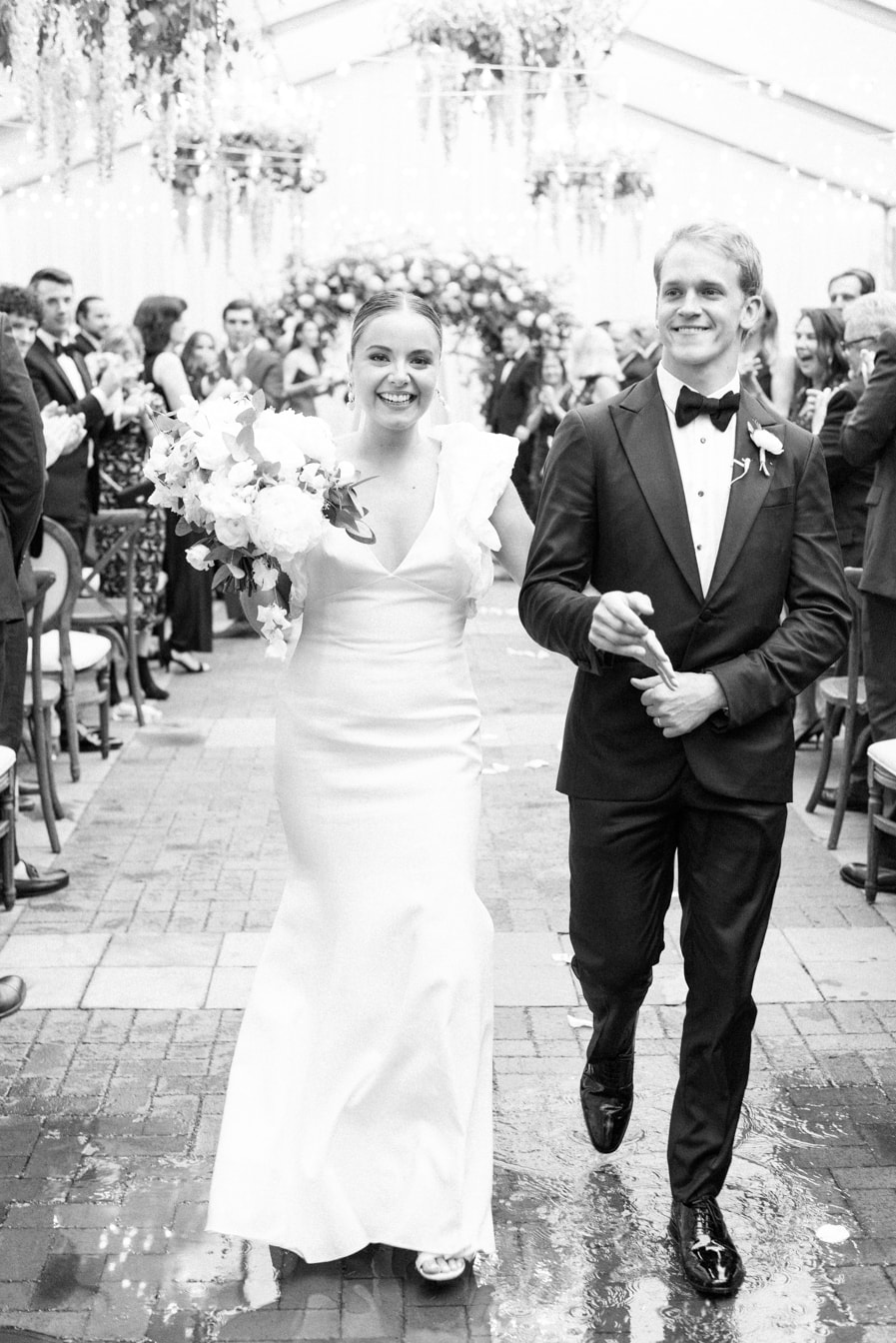 Bride and groom walking down the aisle together after tying their knot