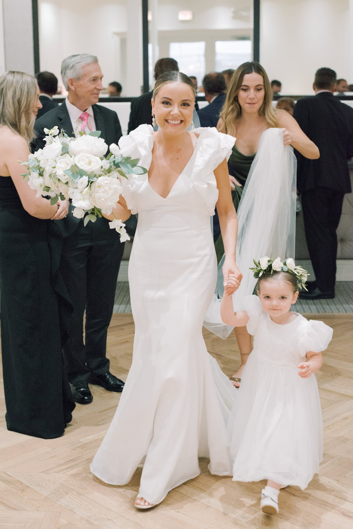 Bride with her flower girl smiling at camera at Chicago Illuminating Company