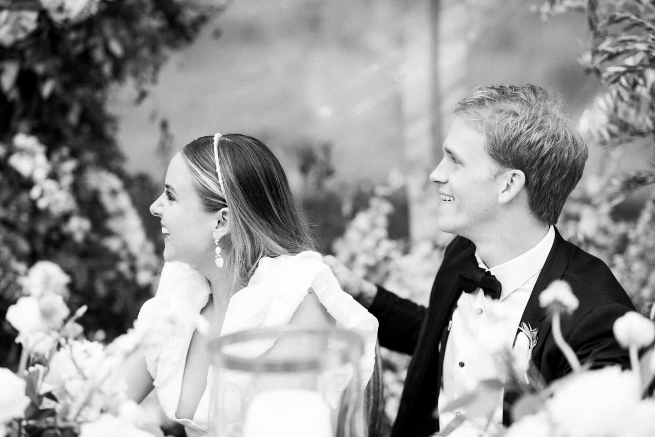 Black and white image of bride and groom smiling during wedding reception