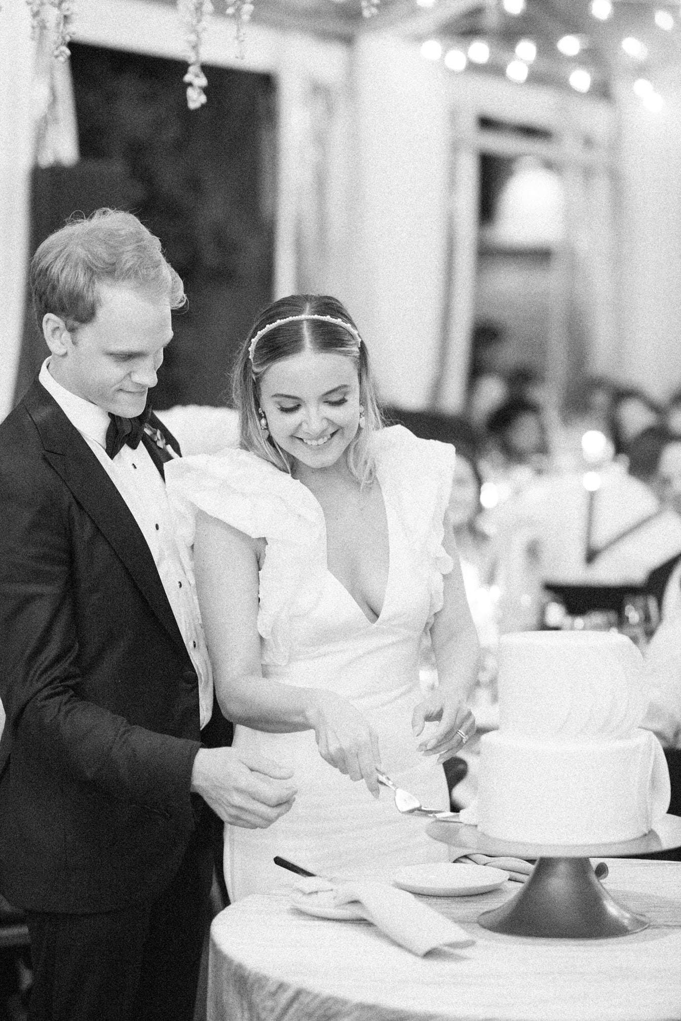 Bride and groom cutting wedding cake during their reception
