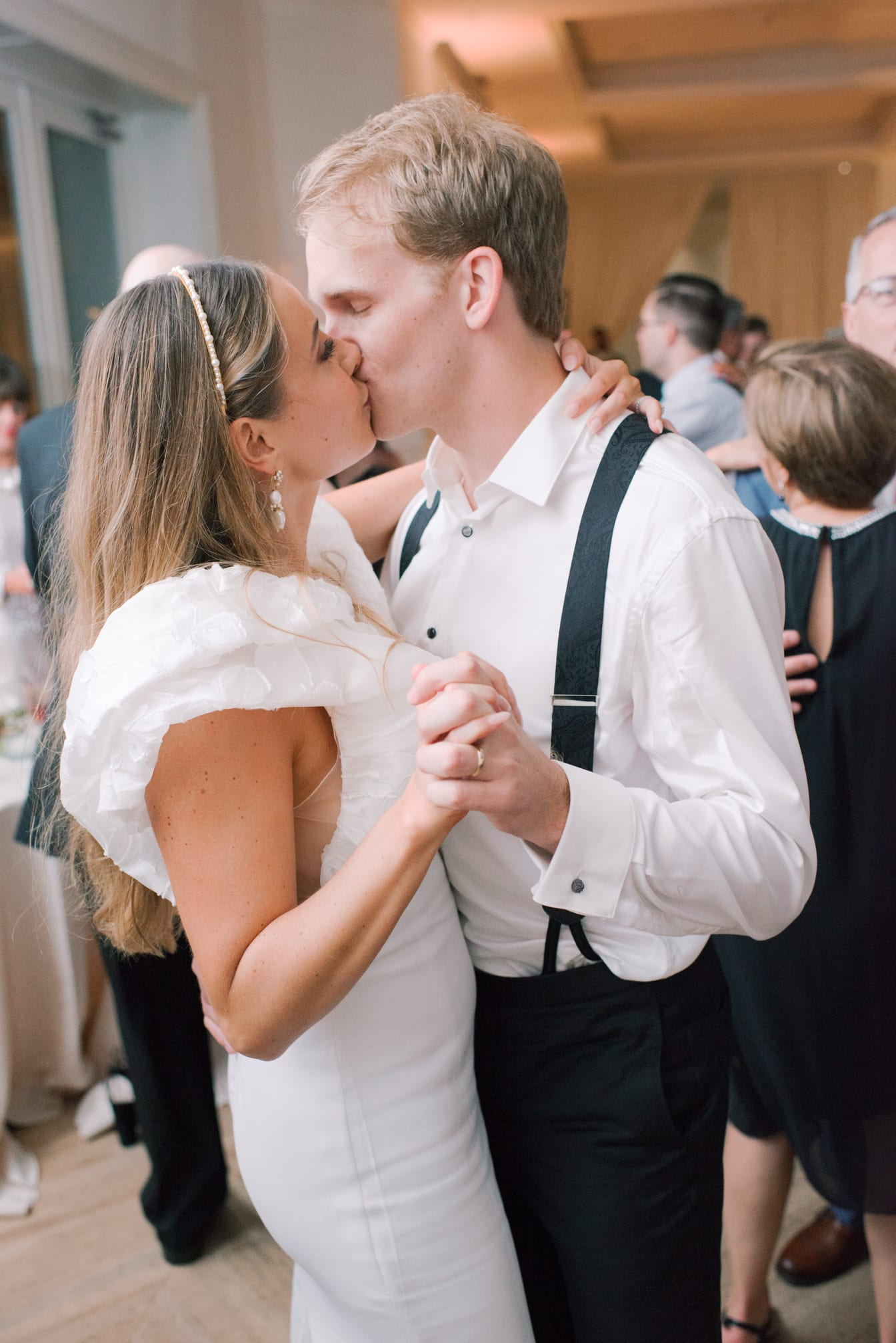 Bride and groom kissing each other during wedding reception while dancing