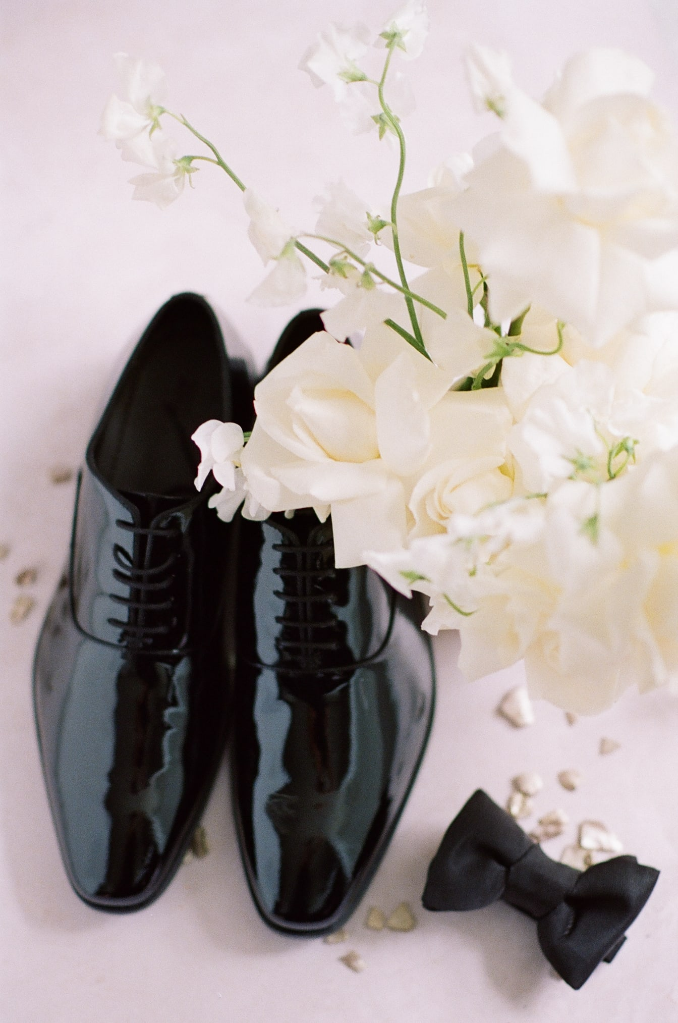 Groom's glossy shoes placed next to bow tie