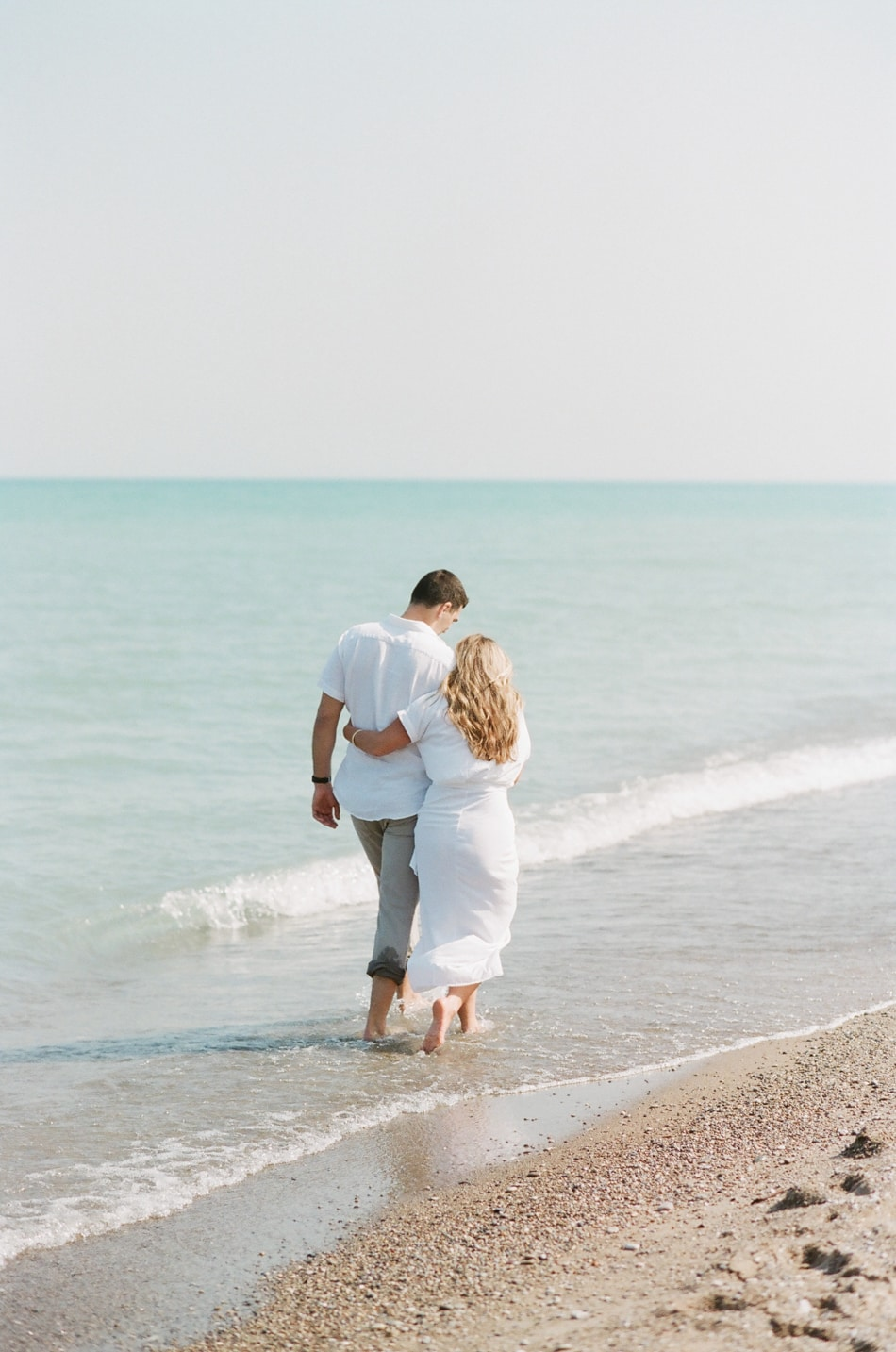 Bride and groom walking on beach in Lake Forest