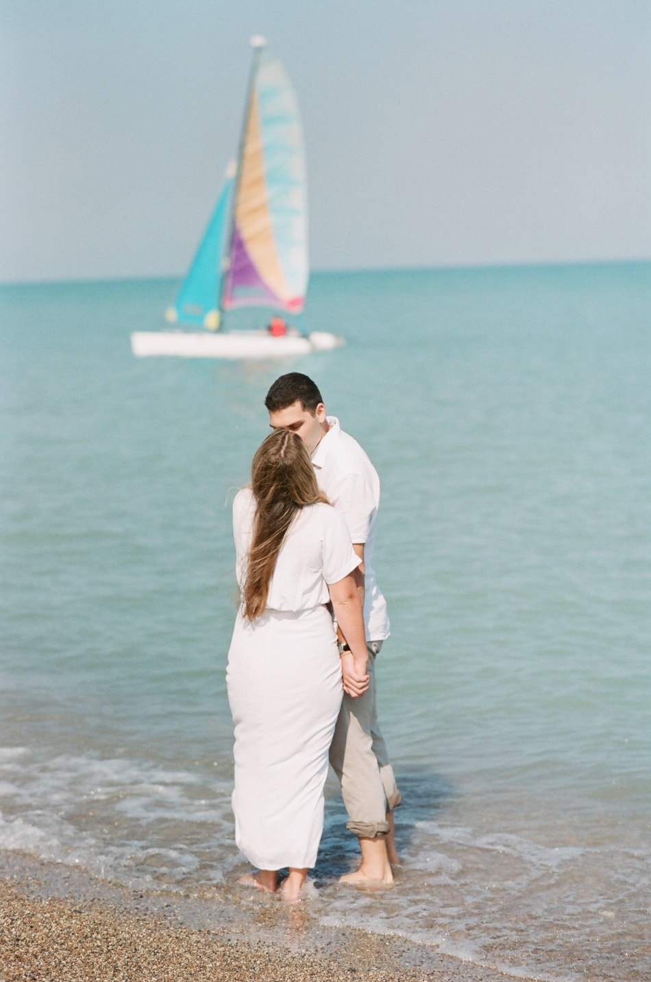 Bride and groom kissing in front of sail boat at Glencoe beach