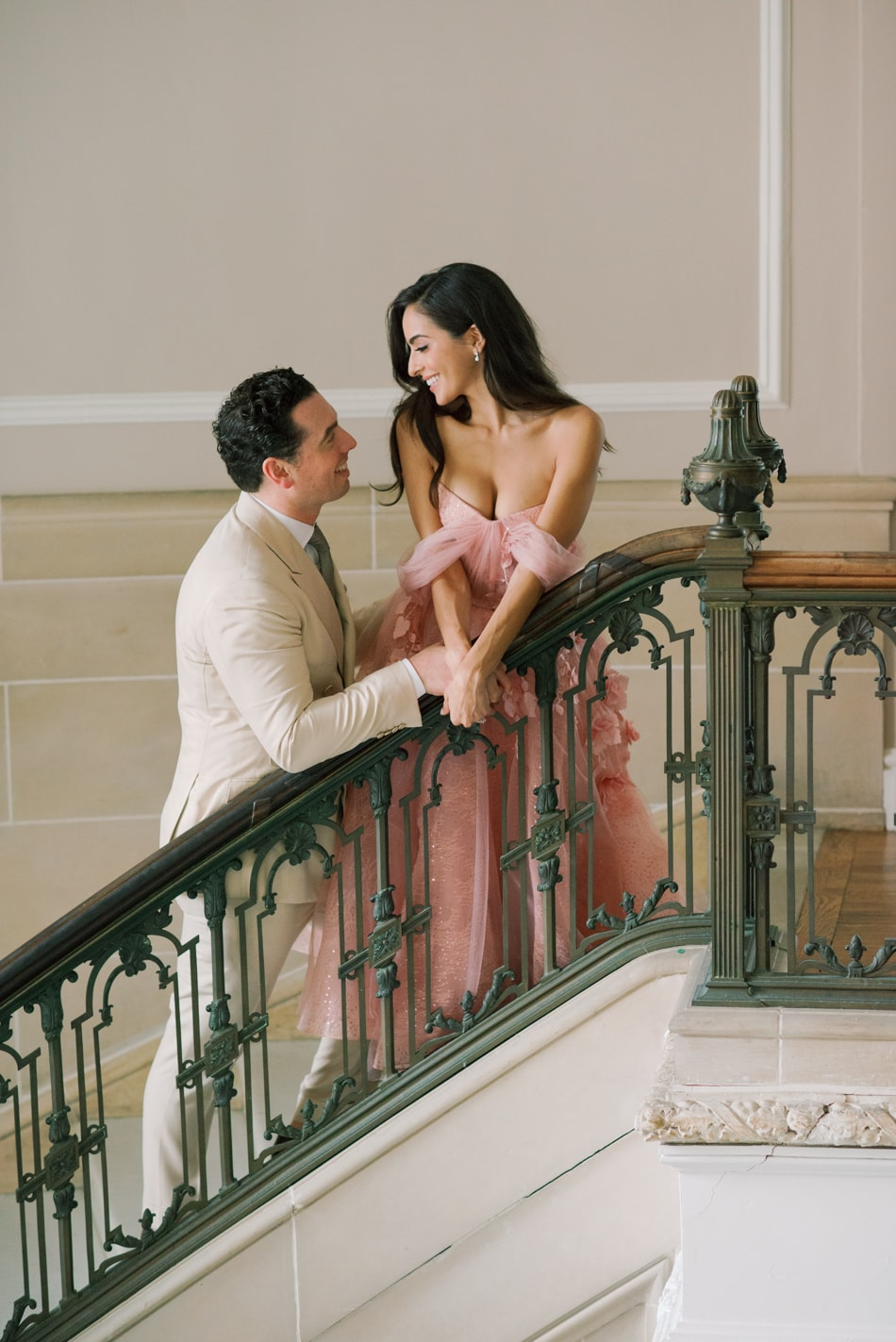 Bride and groom talking to each other on grand stairs at Armour House