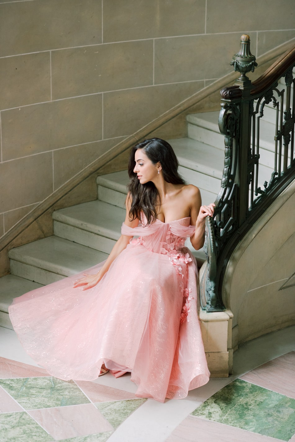 Bride in blush gown sitting on grand stairs at Armour House