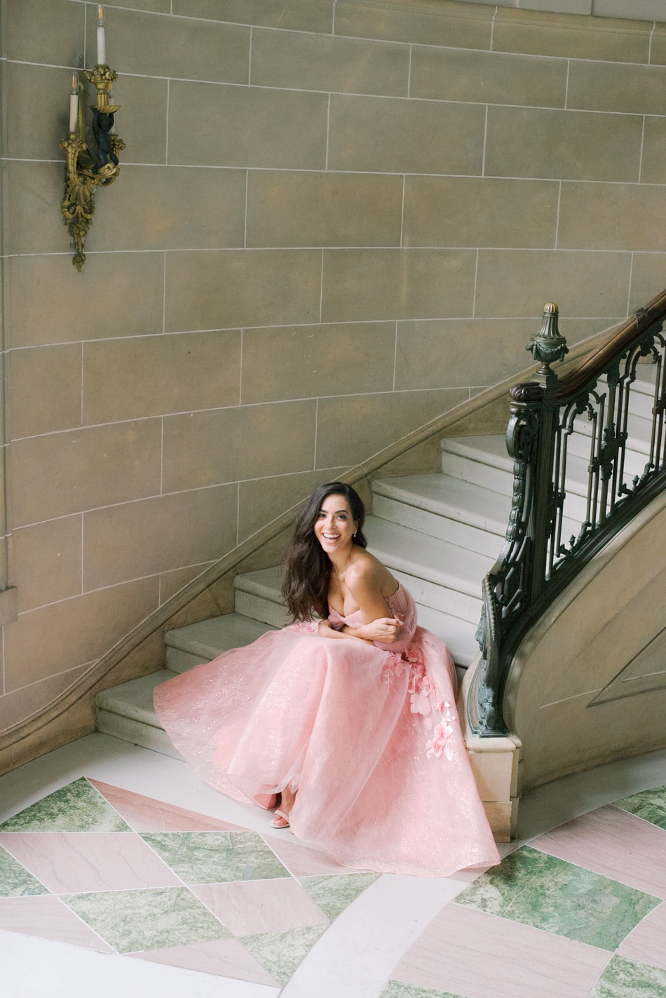 Bride in blush gown sitting on European inspired stairs