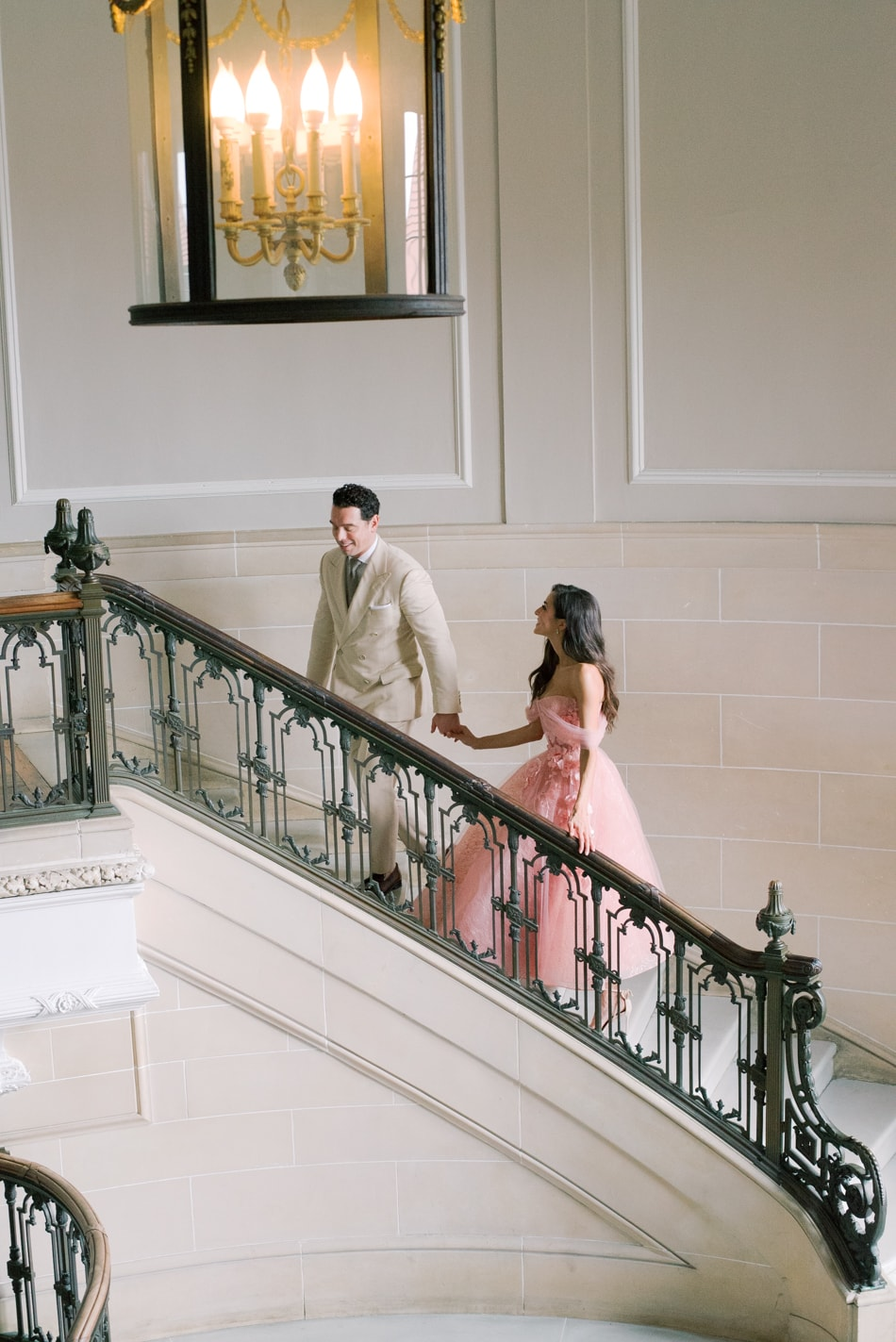 Bride in blush dress walking up the stairs with her groom in Lake Forest